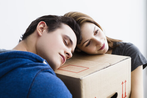 Germany, Munich, Young couple leaning on cardboard box, close up - SPOF000268