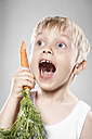 Portrait of boy imitating carrot as telephone, close up - PD000311