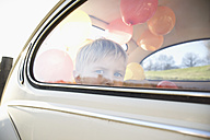 Germany, North Rhine Westphalia, Cologne, Boy in car looking through window, close up - PD000322