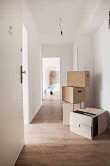Cardboard boxes on corridor while man walking in background - FMKF000531