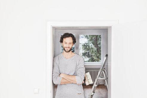 Portrait of man holding brush, smiling - FMKF000540