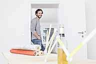 Portrait of man standing by doorway, smiling - FMKF000544