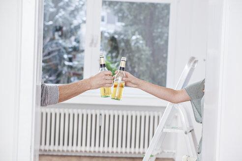 Human hands toasting beer bottles - FMKF000559