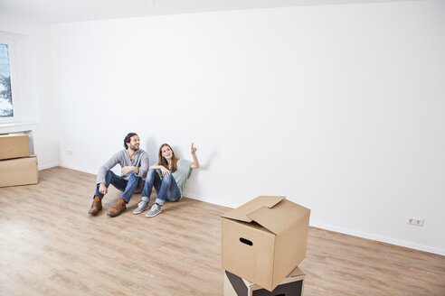 Couple sitting on floor and pointing at wall - FMKF000710