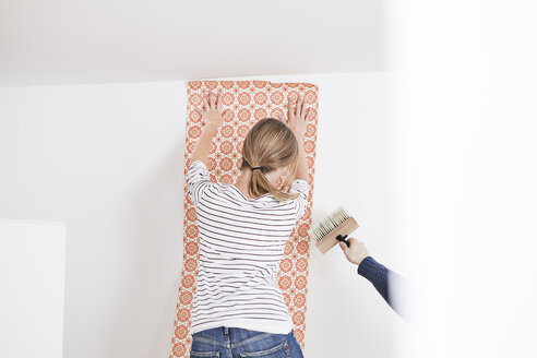 Woman sticking wallpaper on wall - FMKF000632