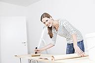 Woman applying glue on wallpaper - FMKF000635