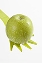 Green apple on fork, close up - CSF017860