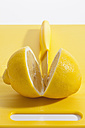 Lemon with knife on plastic board, close up - CSF017951