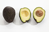 Whole and halved avocado ripe on white background, close up - CSF017972