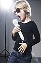 Boy singing in paper mircophone against grey background - ED000010