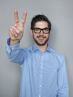 Businessman doing peace sign, smiling - STKF000229