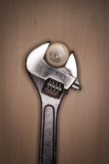 Adjustable spanner with euro coin on wooden background - KJF000209