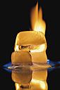 Ice cube burning on black background - MU001297