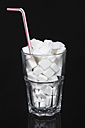 Glass of sugar cubes with drinking straw on black background - MU001284