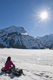 Austria, Woman sitting in snow at Tannheim Alps - UMF000621