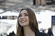 Germany, Cologne, Young woman at airport, smiling - RHYF000274