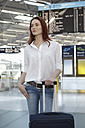 Germany, Cologne, Young woman with luggage at airport - RHYF000275