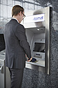 Germany, Cologne, Mature man using cash dispenser machine at airport - RHYF000343