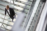 Germany, Cologne, Mature man walking down stairs - RHYF000327