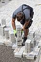 Germany, Rhineland Palatinate, Young man assembling paving stones - CSF018352