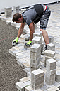 Germany, Rhineland Palatinate, Young man assembling paving stones - CSF018355