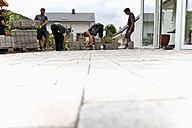 Germany, Rhineland Palatinate, Young men assembling paving stones - CSF018462
