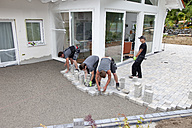Germany, Rhineland Palatinate, Young men assembling paving stones - CSF018465