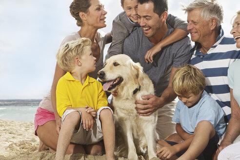 Spain, Family sitting on beach at Palma de Mallorca, smiling - SKF001194