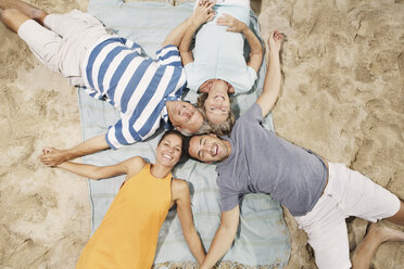Spain, Family lying on beach at Palma de Mallorca, smiling - SKF001243