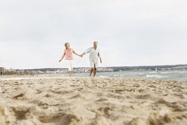 Spain, Senior couple walking on beach at Palma de Mallorca - SKF001181