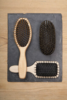 Various hair brushes on slate board, close up - TDF000045