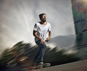 Germany, Cologne, Young man skating on skateboard - RHYF000354