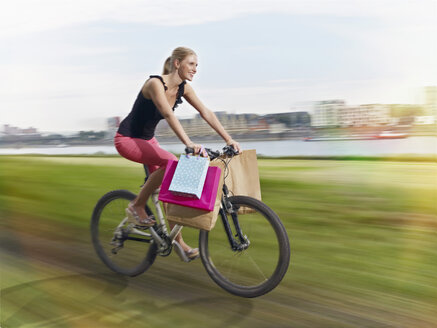 Germany, Cologne, Young woman on bicycle with shopping bags - RHYF000374
