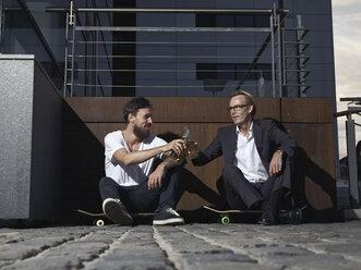 Germany, Cologne, Men with beer bottles - RHYF000373