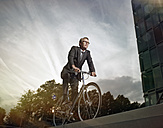 Germany, Cologne, Mature man riding bicycle - RHYF000370