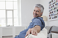 Germany, Bavaria, Munich, Portrait of mature man sitting on couch, smiling - RBF001210