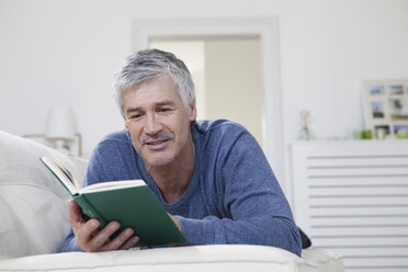 Germany, Bavaria, Munich, Mature man reading book on couch, smiling - RBF001276