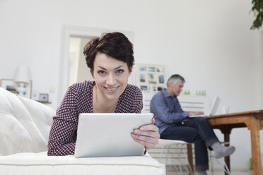 Germany, Bavaria, Munich, Woman holding digital tablet while man using laptop in background - RBF001202