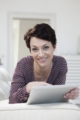 Germany, Bavaria, Munich, Portrait of mid adult woman using digital tablet on couch, smiling - RBF001201
