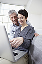 Germany, Bavaria, Munich, Couple using laptop at home, smiling - RBF001306