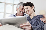 Germany, Bavaria, Munich, Couple using digital tablet at home, smiling - RBF001238