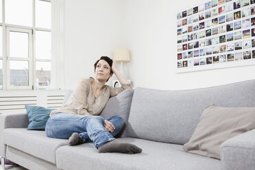 Germany, Bavaria, Munich, Mid adult woman sitting on couch, looking away - RBF001292