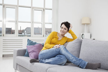 Germany, Bavaria, Munich, Portrait of mid adult woman sitting on couch, smiling - RBF001314