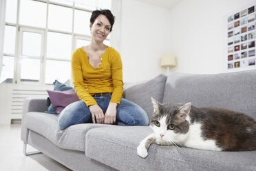 Germany, Bavaria, Munich, Mid adult woman with cat on couch, smiling - RBF001303