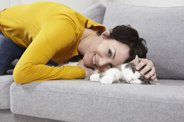 Germany, Bavaria, Munich, Mid adult woman with cat on couch, smiling - RBF001302