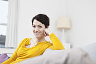Germany, Bavaria, Munich, Portrait of mid adult woman sitting on couch, smiling - RBF001297