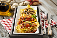 Variety of ravioli filled with tomato, ham and mushrooms on plate - MAEF006421
