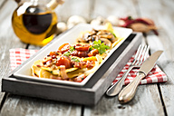 Variety of ravioli filled with tomato, ham and mushrooms on plate - MAEF006423
