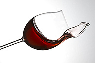Red wine splashing in glass against white background - PSAF000007