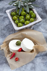 Goat cheese with green olives in olive oil and chili on brown paper, close up - CSF018483
